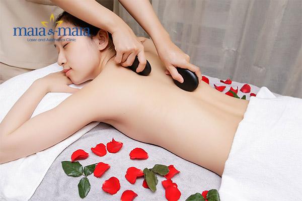 Khách hàng đang được hỗ trợ massage bằng đá nóng